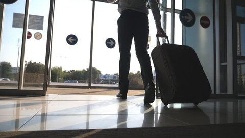 Man going through glass automatic door to the street and roll suitcase on wheels. Businessman walking from the airport with his luggage. Sun flare at background. Trip or travel concept. Slow motion