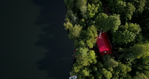 Aerial Drone footage, flying above a secluded lake surrounded by dense forest.  Drone climbs zooming the image out.  A cottage and boat can be seen.