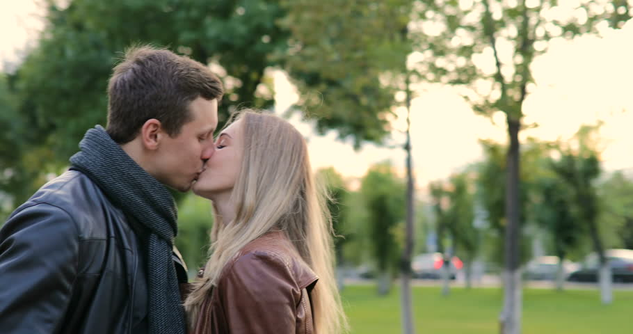 young beautiful couple hugging and kissing in the park