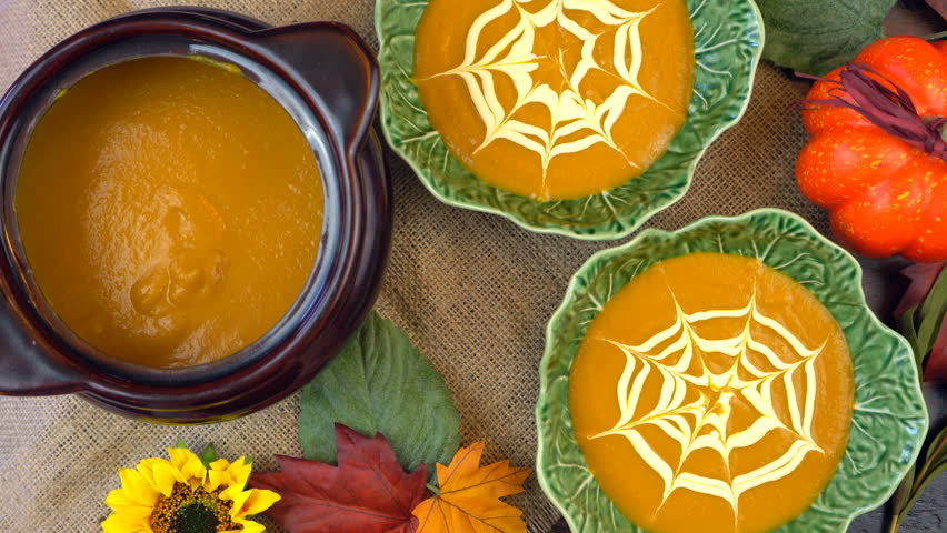 Serving hot pumpkin soup into green leaf bowls and making spiderweb cream decorations, on a rustic background for Happy Halloween party food, adding spiders real time.