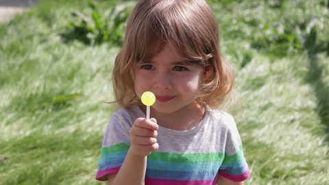 little pretty girl eating caramel lollipop on a background of green grass and smiling