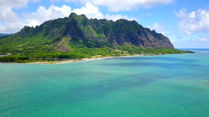 Aerial Scenic flyover footage of ocean of Chinamans Hat, Oahu Hawaii.  Tropical view of Kualoa Valley, Koolau Mountain. Kaneohe Bay side. Turquoise-blue water lovely with blue sky. 4K UHD drone shot.   Shutterstock HD Video #30760324