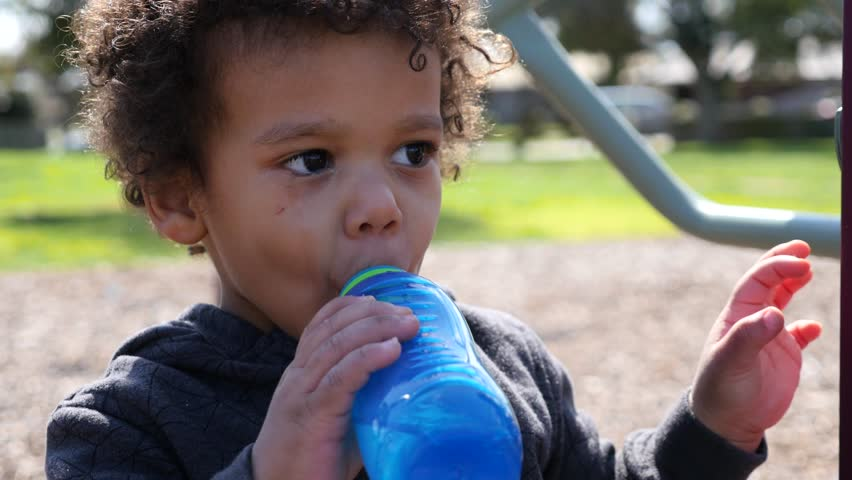 Sad, crying male child drinking from a water bottle