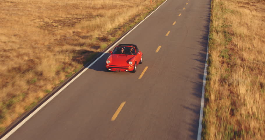 Aerial View Of Couple Driving Red Convertible  Sports Car Down Country Road At Sunset