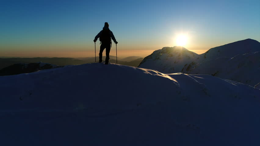 Aerial - Raising above male hiker standing on top of snowy mountain and looking at beautiful sunset | Shutterstock HD Video #30772960