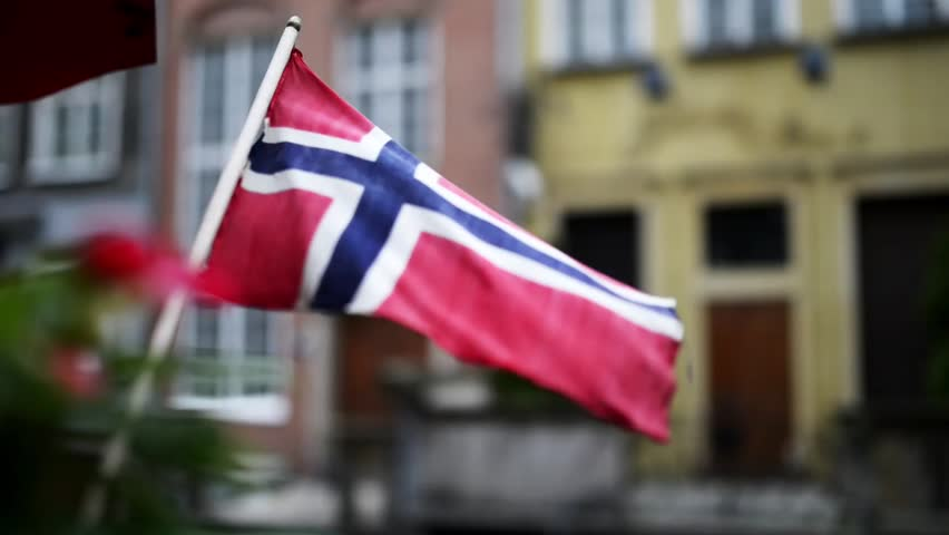 Flag of Norway flutters in wind on facade of administrative building.