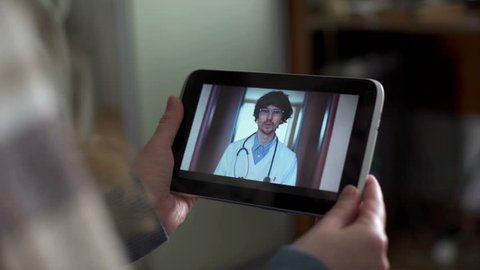 Woman In Kitchen Using Tablet - Online Chat with Doctor on Screen