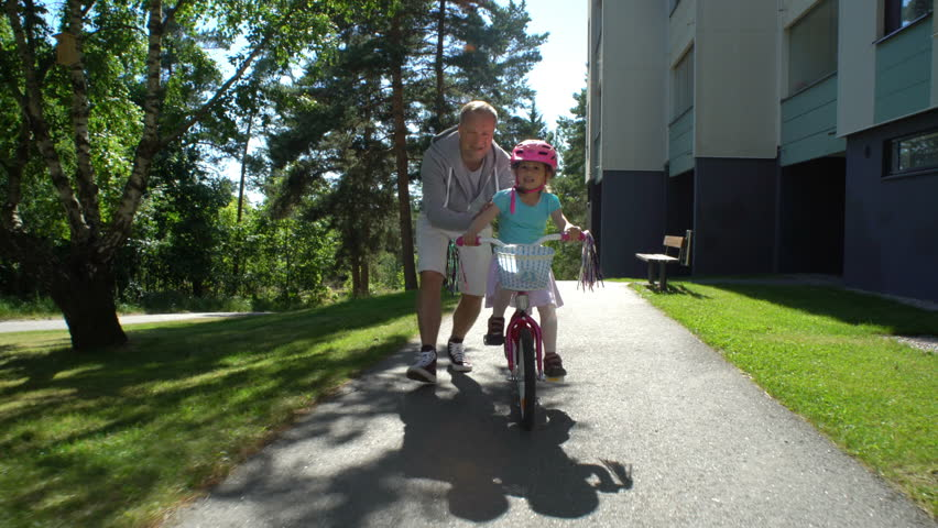 First cycling. Dad teaches his daughter to ride a bike.