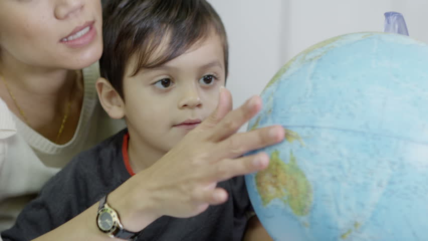 An attractive mother of Asian ethnicity uses a globe to show her young son the countries of the world. In slow motion.