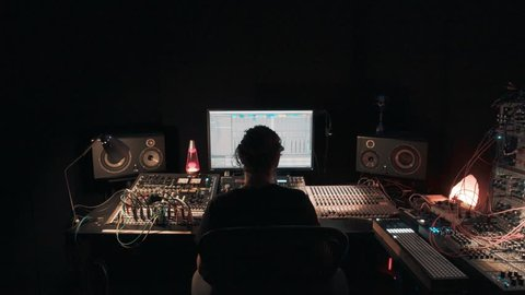 Young professional creative music or songwriter creates tunes for project, in dark room workstation studio uses computer software and recording devices, multiple cables and lights