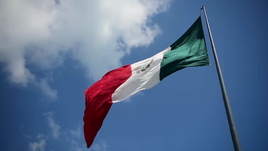 Giant mexican flag flies in the wind in Cancun. Shot in Yucatan, Mexico