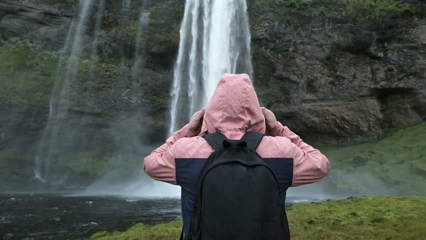 Tourist man in a red jacket stands and looks at a stream of falling water. Beauty in nature