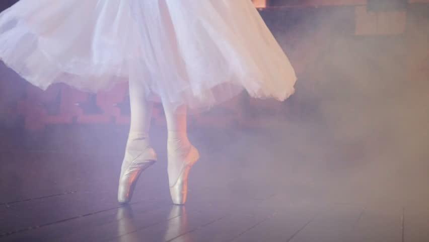Dancing ballerinas feet in a fogged room.