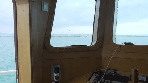 Day view at sea port from wheelhouse window. Beakon and