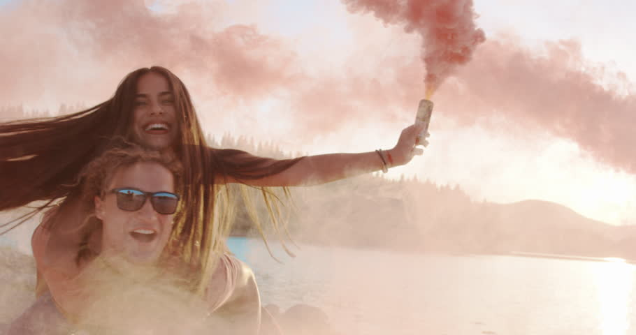 Attractive Young Happy Couple Man Holding Woman On Piggyback At Lake Shore Having Fun With Smoke Flare Sunny Day Summer Romantic Vacation Happy Family Concept Slow Motion Shot On Red Epic W 8k