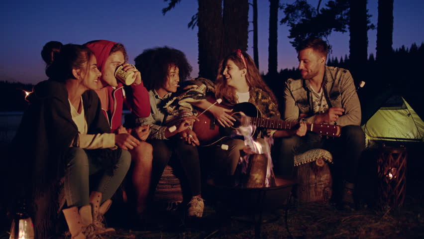 Diverse Group Of Attractive Young People Playing Guitar Around Burning Bonfire In The Woods Clapping Drinking Laughing And Joking Music Vacation In Nature Romantic Musical Getaway Concept Slow Motion #30848410