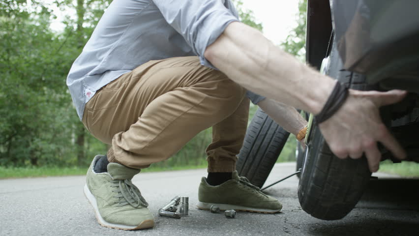 Young Man Walking With the Tire to the Trunk | Shutterstock HD Video #30877300