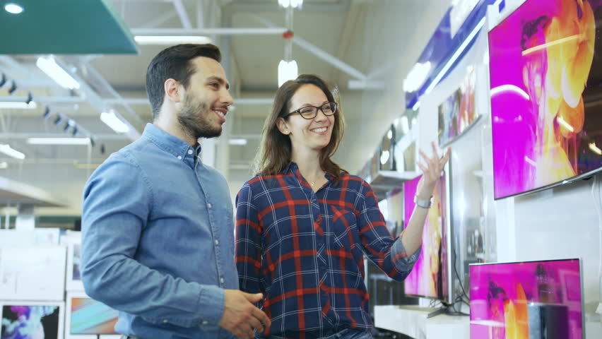 Young Couple Shopping for a New 4K TV Set in the Electronics Store. They're Trying to Decide on the Best Model But Have Doubts. Shot on RED EPIC-W 8K Helium Cinema Camera. | Shutterstock HD Video #30883930