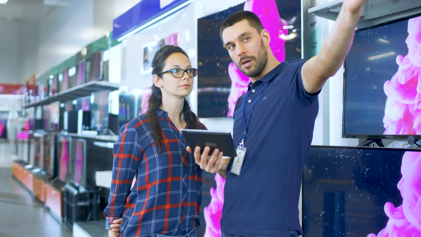 In the Electronics Store Professional Consultant Provides Expert Advice on Tablet Computer Specifications For Beautiful Young Woman. Store is Bright, Modern and Has all the Latest Devices. 4K UHD. | Shutterstock HD Video #30883942