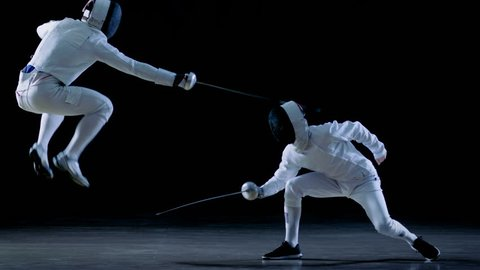 Two Professional Fencers Show Masterful Swordsmanship in their Foil Fight. They Dodge, Leap and Thrust and Lunge. Shot Isolated on Black Background and in Slow Motion. 4K UHD.