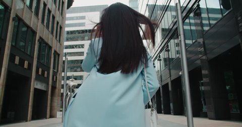 epic Steadicam shot of a young beautiful Asian girl with smartphone going to work around office buildings, back view, flowing hair