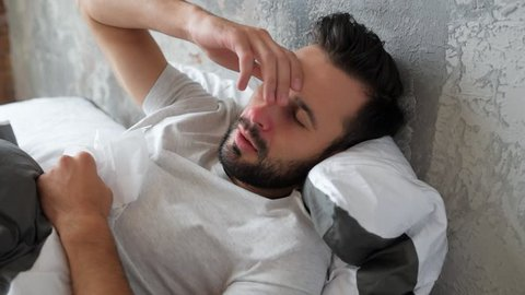 Sick millennial guy lying in bed and sneezing