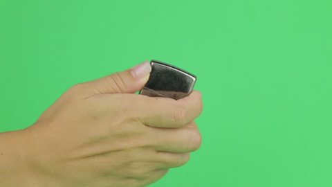 Hand Lighting up a zippo Lighter. Ignites the lighter on a green screen. Using a lighter on a green screen.