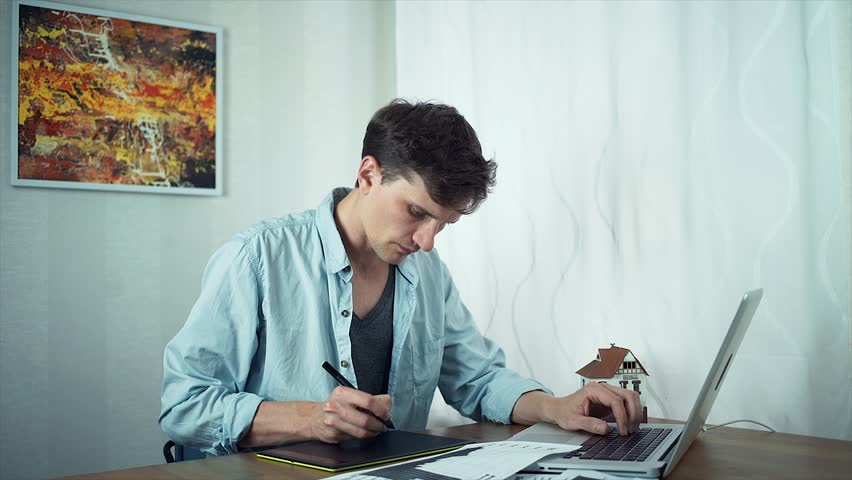 Creative graphic designer sketching on tablet housing project using laptop. Freelancer working at home office. Modern abstract picture at wall behind | Shutterstock HD Video #30910309