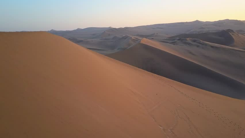 Aerial drone footage on a sunny day above sand dunes of Peru. Close to Ica and Huacachina. Similar to Sahara and Emirates Deserts. Boogie cars driving and people sandboarding. Oasis nearby.   Shutterstock HD Video #30910507
