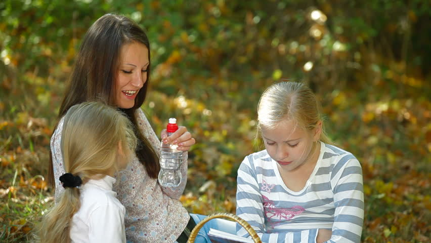 Young mother and two daughters enjoying autumn day at picnic in the park, children drinking water