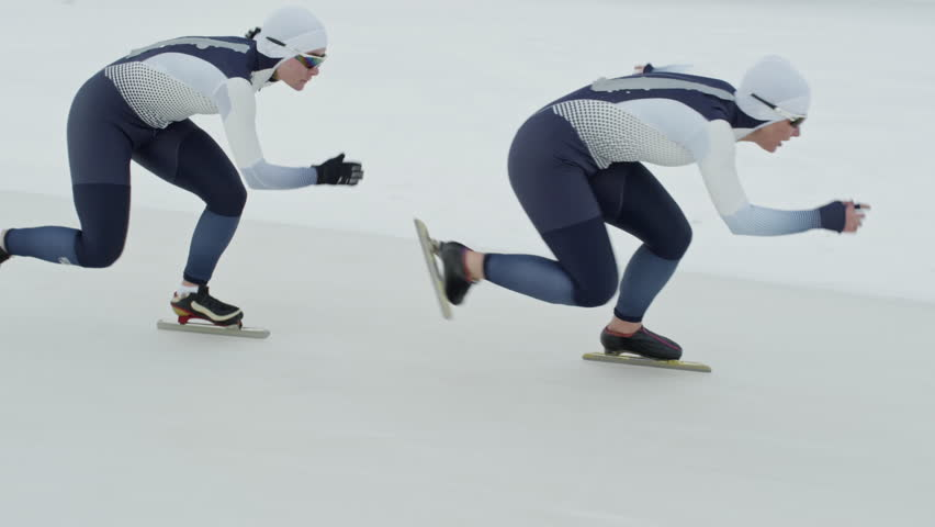 Tracking with slow motion of professional female speed skaters wearing spandex full-body covering suits sprinting along track in ice rink #30923680