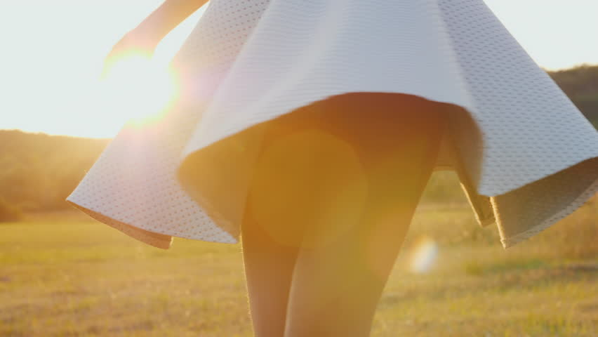 A young slim woman in a light skirt is spinning in a meadow. At sunset, slow motion video