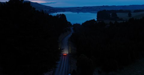Aerial view car driving on country road at dusk through forest with headlights