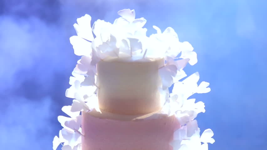 White wedding cake with bright light in the restaurant, close-up. Close-up of white wedding cake with flowers.