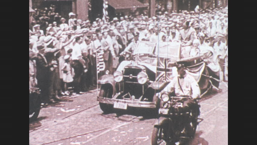 1930s: Car with flags, motorcycles parade through clapping street crowd. Women speak from crowd. Man waves from passing parade car. Bobby Jones speaks into radio microphone, surrounded by men.