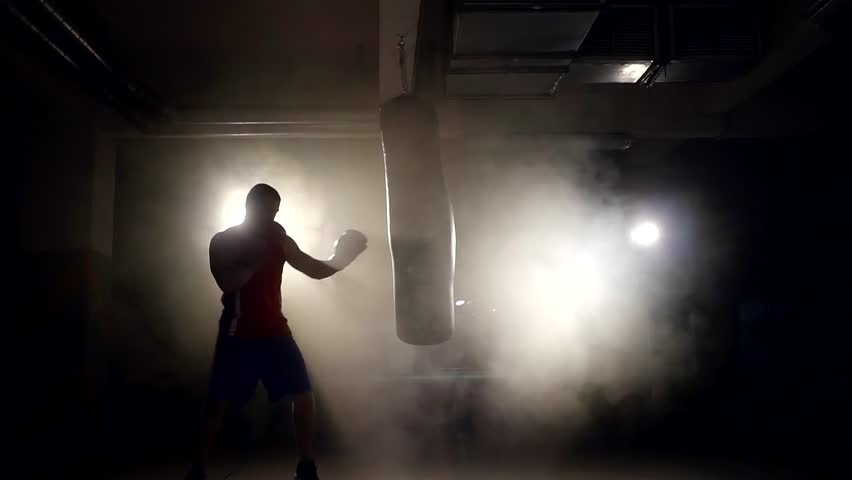 alone large boxer is working out blows on a punching bag in a dark gym #30958360
