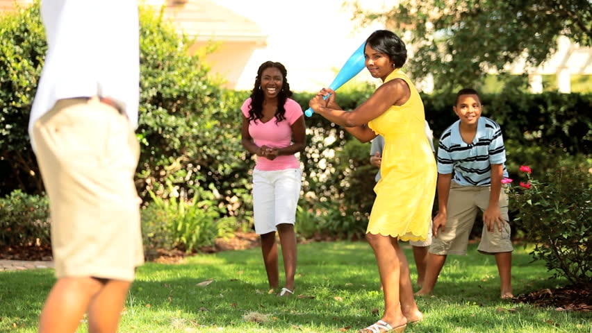 Diverse happy family playing baseball in garden
