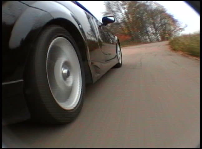 Black sport car in motion by the road. View from on-board camera on weel and wing  | Shutterstock HD Video #309706