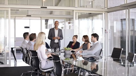 Manager training people about company and future prospects. Group of businesspeople sitting in meeting room and listening to the speaker. Leader man training his work group in a conference room.