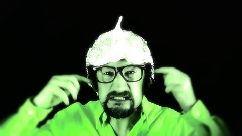 An angry man wearing a tin foil aluminium hat (believing that it shields  the brain from threats such as electromagnetic fields, mind control or  reading)  green coloring