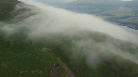 Aerial footage sweeping over a misty summit cairn on the shores of Ullswater, Lake District