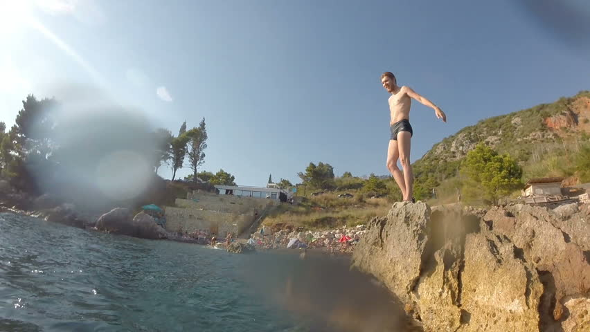 Athletic Young Man Jumping From Cliff Into Ocean Sea Water Muscular Adventure Extreme Sports Lifestyle Hobby Vacation Clear Beach Slow Motion Leisure Activity Gopro