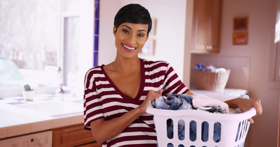 Portrait of cheerful black female holding laundry basket inside kitchen, laughing at camera. Happy young mother doing chores at home. 4k