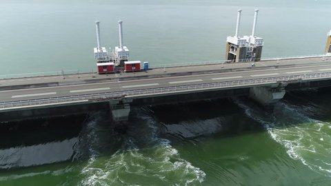 Aerial view of Eastern Scheldt storm surge barrier Oosterscheldekering flying right showing traffic driving over largest of 13 ambitious Delta Works series of dams and storm surge barriers in Zeeland