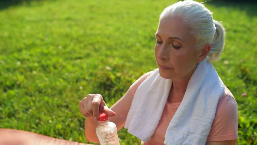 Delighted aged woman drinking water after sport activities | Shutterstock HD Video #31035082