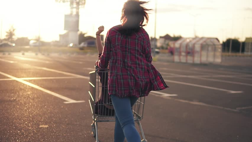 Back view of a young woman pushing the grocery cart, while her friend is sitting inside during sunset. Lens flare. Slowmotion shot
