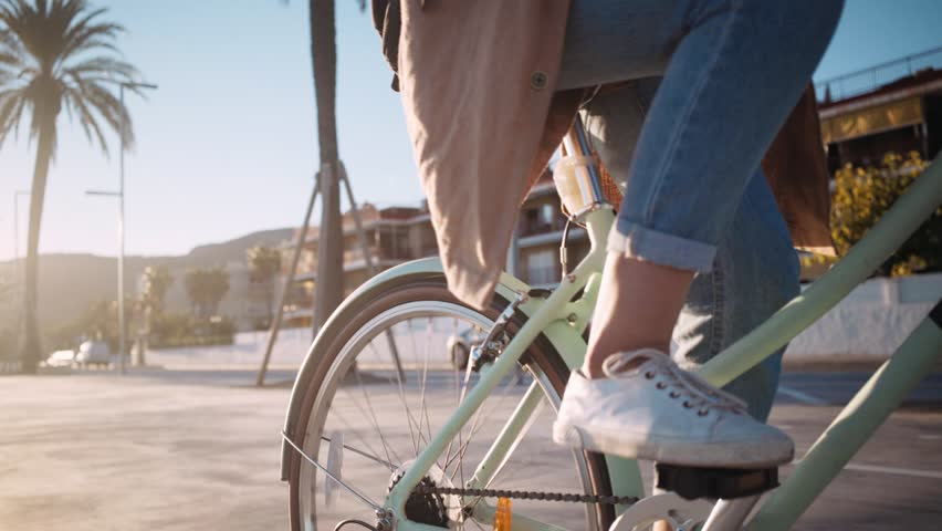 Beautiful summertime mood shot of young woman or girl riding bicycle through beach promenade, in stylish outift, pedalling next to palm trees in sunset light, concept youth and miami | Shutterstock HD Video #31052050