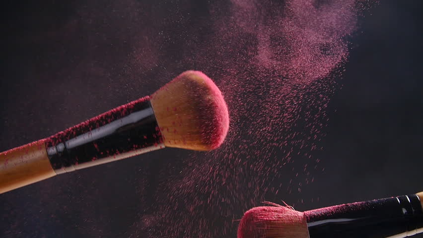 Two makeup brushes with powder on a dark background
