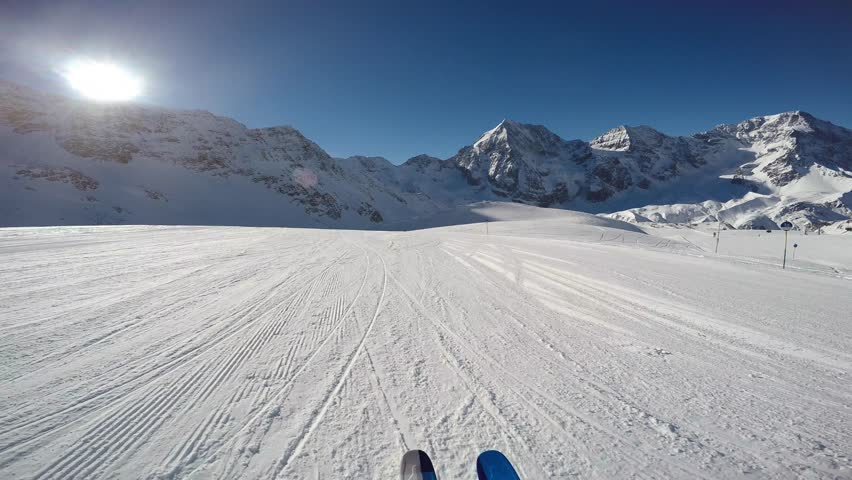 Skiing along a snowy ridge. In background blue cloudy sky and shiny sun and Tre Cime, Drei Zinnen in South Tirol, Dolomites, Italy. Adventure winter extreme sport. POV Camera.