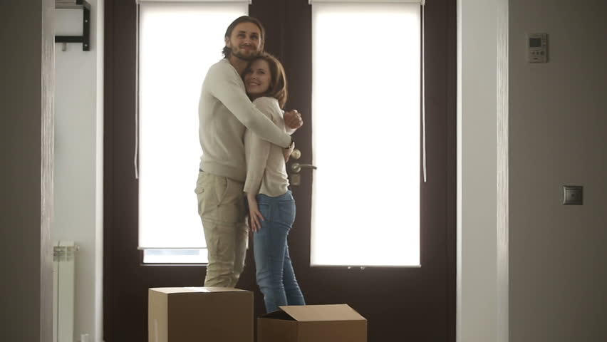 Happy family couple holding boxes opening door entering new luxury house, excited married property owners moving with belongings into own home, looking around rented bought residence and embracing